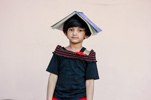 Little indian / asian girl keeping book on over head