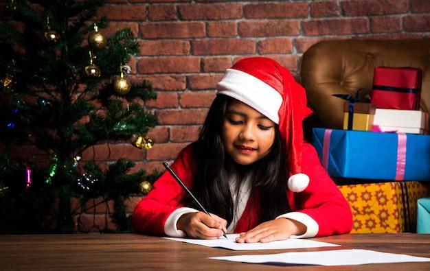 어린 인도 아시아 소녀는 크리스마스에 산타에게 편지를 쓰고 집 바닥에 선물을 들고 앉아 있다