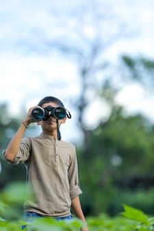 小さなインドの少年は双眼鏡で自然の中で楽しんでいます
