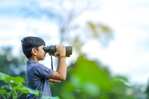 Маленький индийский мальчик наслаждается природой в бинокль