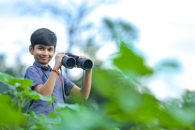 Little indian boy enjoys in nature with binoculars