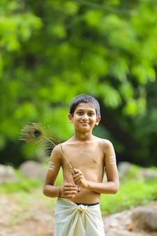 Little indian boy posing as lord krishna