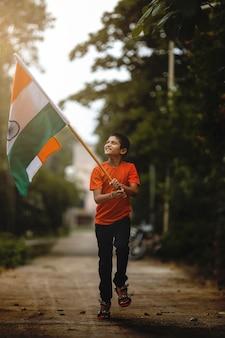 Маленький индийский ребенок, держащий, размахивающий или бегущий с трехцветным флагом