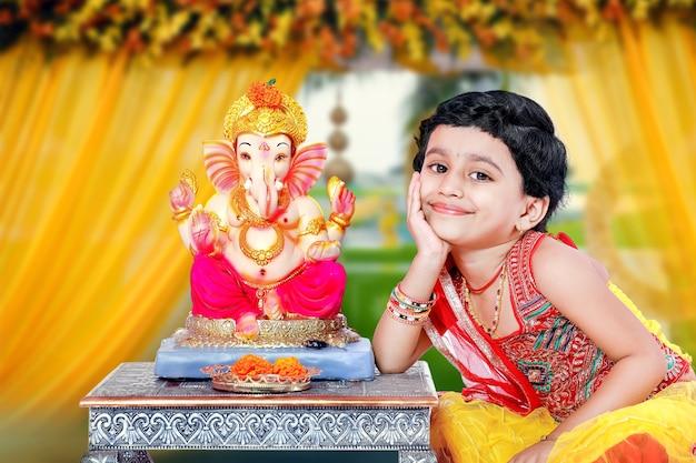 Маленькая индийская девочка с лордом ганешей и молящимися, индийский фестиваль ганеша