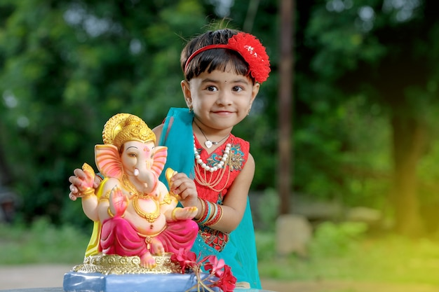 Little indian girl child with lord ganesha and praying