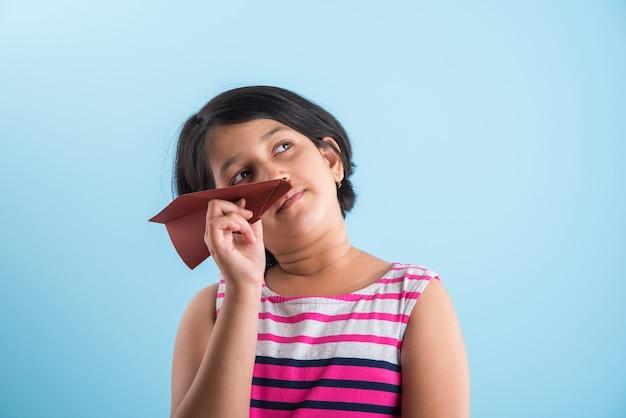 종이 비행기를 가지고 노는 어린 인도 소녀, 파란색 배경 위에 종이 비행기를 비행 아시아 소녀