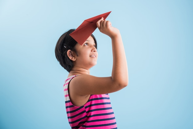 Little indian girl playing with a paper plane, asian girl flying paper plane over blue background