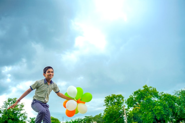 Little indian school boy jumping in sky with tri color balloons and celebrating independence or republic day of india