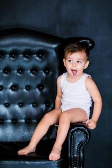 赤いハートの風船と肘掛け椅子に座っている白いtシャツで2歳の小さな幼児男の子