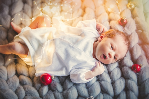 Little infant with christmas baubles around