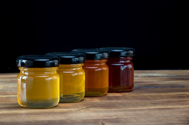 Little jars with honey different colours on wooden table