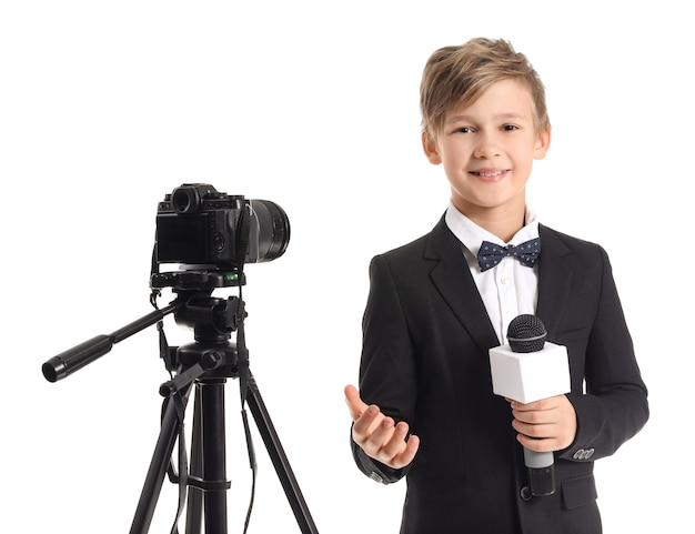 Little journalist with microphone and camera on white surface