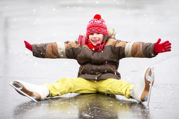 スケートをしていると、うれしそうな男の子が倒れました。子供は冬に氷の上でスケートをしている。