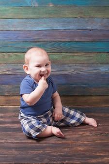 색상 나무 배경에 그의 입에 그의 손가락으로 작은 즐거운 소년