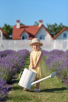 Маленькая радостная девочка в желтом платье с лейкой в саду лаванды