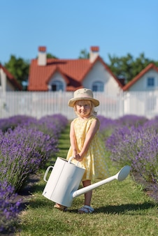 Little joyful girl in yellow dress with watering can at lavender garden