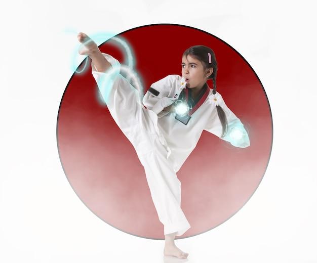 어린 가라테 소녀가 일본 국기의 배경을 차고 있습니다. 잠재적인 힘의 개념. 정기적인 훈련과 의지력