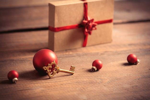 Little key and christmas box on wooden table