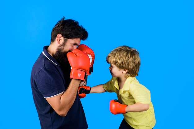 Little kickbox fighter hitting with his coach dad and his son in boxing gloves child and instructor