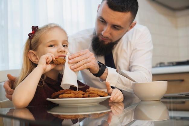 小さな子供と父親が顔を掃除している間、キッチンでビスケットを食べています。朝の台所での食事の父と娘。
