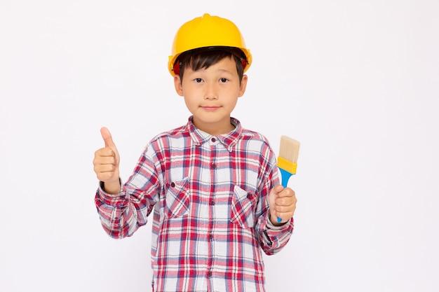 그의 손에 페인트 브러시와 노란색 헬멧을 쓰고 건설 노동자로 작은 아이. 흰색 배경 스튜디오 그림입니다.