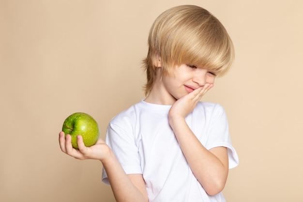 Маленькая блондинка малышка в белой футболке держит зеленое яблоко на розовой стене
