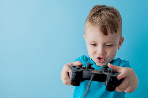 Little kid boy 2-3 years old wearing blue clothes hold in hand joystick for gameson blue children studio portrait. people childhood lifestyle concept. mock up copy space.