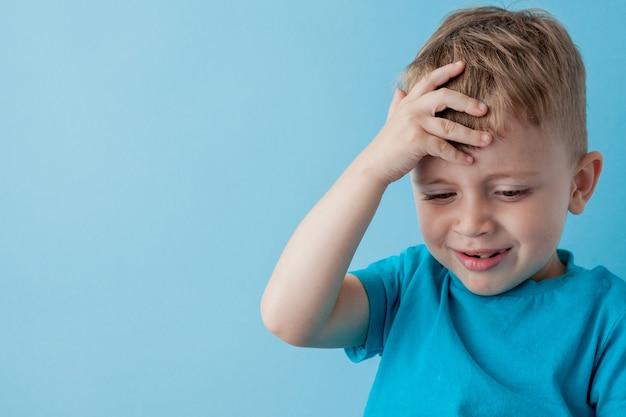 파란색 옷을 입고 작은 아이 소년 2-3 세 gameson 파란색 배경 어린이 스튜디오 초상화에 대 한 조이스틱을 손에 개최. 사람들이 어린 시절 라이프 스타일 개념. 복사 공간을 모의
