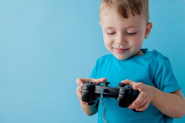 青い服を着ている2〜3歳の小さな男の子は、ゲームソンの青い背景の子供たちのスタジオの肖像画のジョイスティックを手に持っています。