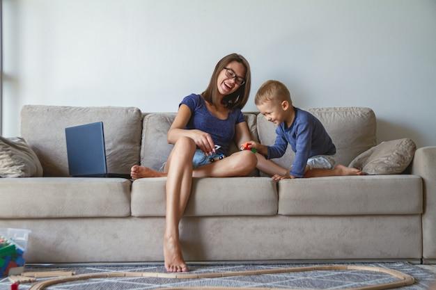 子供男の子と彼の母親がソファーに座って一緒に遊んで