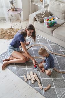 子供男の子と彼の母親は床に座って鉄道で遊んで