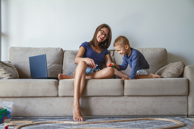 Little kid boy and his mother playing together sitting on the sofa