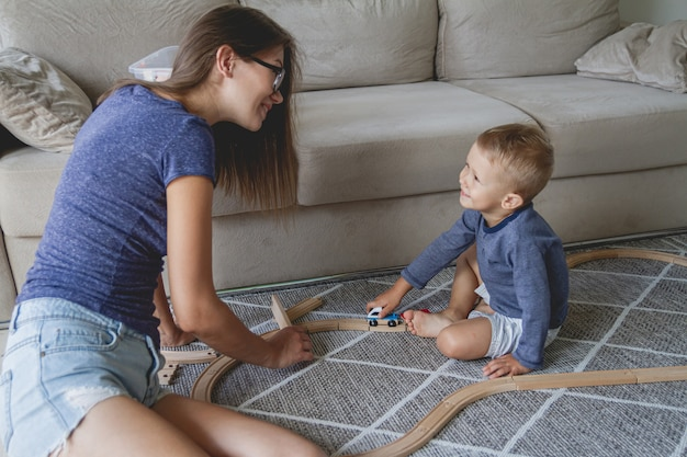 Little kid boy and his mother playing with railway sitting on the floor