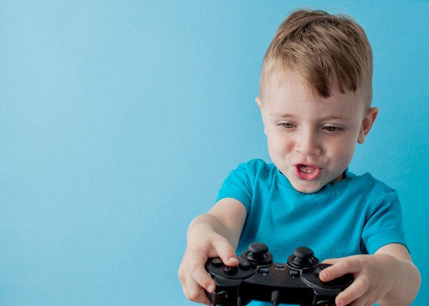 Little kid boy wearing blue clothes hold in hand joystick for games, children studio portrait. people childhood lifestyle concept. mock up copy space