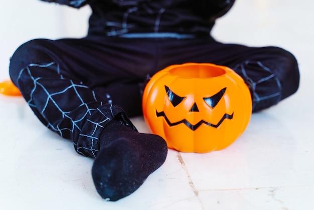 Маленький ребенок собирает конфеты в оранжевой тыквенной корзине на хэллоуин