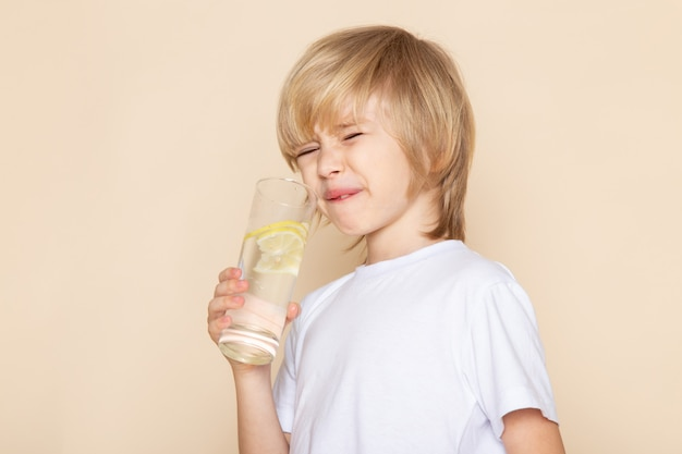 Little kid cute adorable drinking lemon juice in white t-shirt on pink wall
