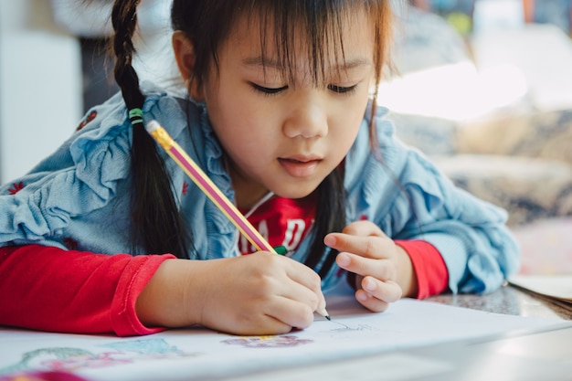 어린이의 창의적인 예술과 손 쓰기 능력을 향상시키는 데 좋은 활동 인 연필로 만화를 그리는 어린 아이. 교육 및 학습을위한 개념.