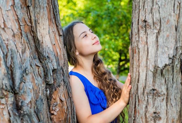 Маленький ребенок-мечтатель с длинными волнистыми волосами и красавицей мечтает о стволе дерева в летнем парке, будущее.