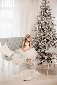 장난감이있는 크리스마스 트리 옆에있는 소파에 공주처럼 옷을 입은 어린 아이