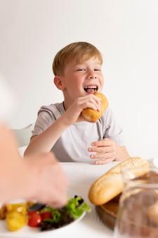 Ragazzino che mangia a una riunione di famiglia