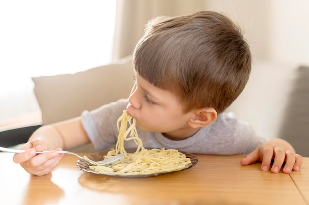 Маленький ребенок ест спагетти