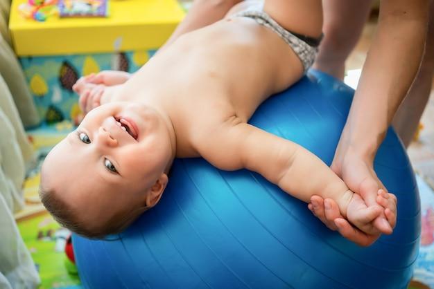 Little kid enjoying exercises on big blue fitness ball