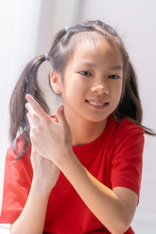 Little kid girl apply hand cream sanitizer gel on her hands for skin care and protection.