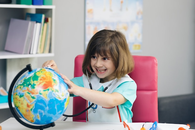 Little kid girl dressed in a doctors suit measures the temperature of the earth.