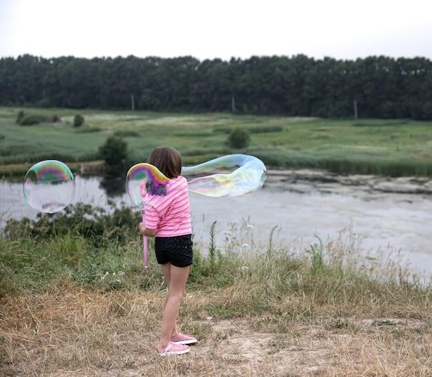 La bambina lancia enormi bolle di sapone sullo sfondo della bellissima natura.