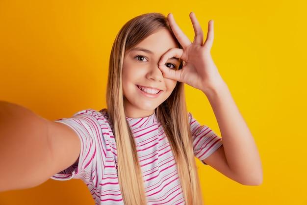 Маленькая девочка ребенка делает фото селфи хорошо знаком монокуляр, изолированные на желтом фоне