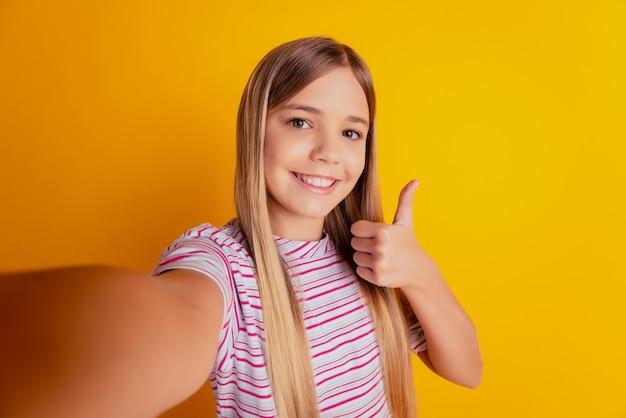 Маленькая девочка ребенка делает фото селфи шоу большой палец вверх знак, изолированные на желтом фоне