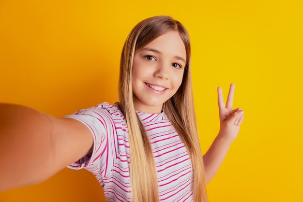 Little kid girl make photo selfie show v-sign isolated over yellow background