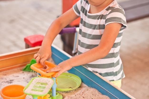 砂とおもちゃで屋外の遊び場で遊んでいる小さな子供の女の子