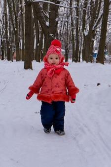 雪の上を走っている小さな子供の女の子。